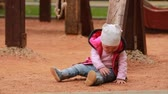 Cute little baby girl dressed in the pink clothing sitting on the playground in outdoor.