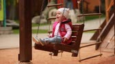 Adorable baby girl enjoying a swing ride on a playground in the city park. Vídeos