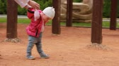 The first steps of little cute baby-girl on the playground in the city park. Vídeos