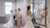 evlenmek : pretty young woman is choosing a wedding dress in the shop and the shop assistant is helping her. Group of Girls in wedding shop.