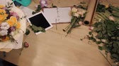 frezja : Male florist making bouquet at flower shop on wooden table, top view of hands with flowers, tablet, roses and decorating paper.