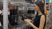 crock : smiling european woman chooses pans in shop cookware supermarket, happy brunette girl in store
