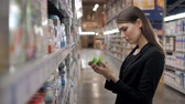 sorts : Happy female shopper searching for baby food in supermarket, yong mother mom in shop