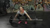 snatch : Portrait of Female performing deadlift exercise with weight bar. Confident young woman doing weight lifting workout barbell at crossfit gym.