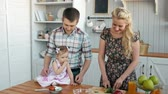 orangejuice : Family eating healthy breakfast in kitchen, happy family mom mother and dad father with little girl child morning with fresh fruits and juices