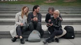 четыре человека : Group of four friends laughing out loud outdoor, sharing good and positive mood, happy friends students on street park, university campus, phone smiling people