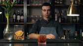 citrus fruit recipes : Close up shot of bartender hands preparing negroni cocktail with grapefruit. He is putting grapefruit skin into the cocktail glass on counter.