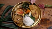 naan : Assorted indian sri-lanka food set on wooden background. Dishes and appetisers of indeed cuisine, rice, lentils, paneer, samosa, spices, masala. Bowls and plates with indian food top view chicken carry Stock Footage