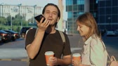 Leisure, technology, communication and people concept - young man and woman using voice command recorder helper or calling on smartphone at street, students voice recognition message with coffee Stok Video