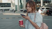 Portrait of smiling woman using smartphone voice recognition. Young Caucasian girl walking with earphones and making audio call outdoors. Mobile software concept, audio helper sunset skyscrappers