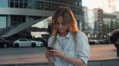 mikrofon : Portrait of smiling woman using smartphone voice recognition. Young Caucasian girl walking with earphones and making audio call outdoors. Mobile software concept, audio helper sunset skyscrappers