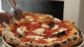 hams : Chef in the pizzeria prepares a pizza and decorates it with parmesan cheese pepper and basil. Stock Footage