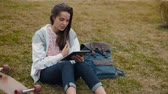 スケーター : Young girl student with backpack and skateboard laying on grass with books and doing homework at outdoor park