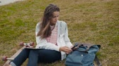planche à roulettes : Young girl student with backpack and skateboard laying on grass with books and doing homework at outdoor park