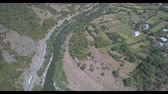 грузоперевозки : Cars drive along the road along the river. Aerial video shooting in Georgia.