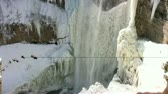 Tilt view of waterfall covered with icicles, the entire Tews Falls during the winter time.   Стоковые видеозаписи