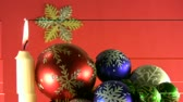 Burning candle and coloured balls in basket and snow flake ornaments traditional Christmas and New Year Eve decoration.  Стоковые видеозаписи