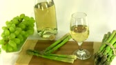 Glass with white wine and sides grapes over the dish and asparagus over wooden cutting board over white background.