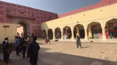 ассортимент : Jaipur, India - November 04, 2019: City Palace tourists pass by shopping rows 4K