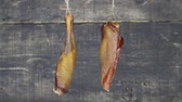 roast ham : Smoked Meat Hanging And Swaying Against Wooden Background Stock Footage