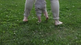 anyaság : Little baby boy learns to walk on grass with mom Stock mozgókép