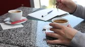 bar : Woman having a coffee in cafe while making notes in daily planner business agenda Dostupné videozáznamy