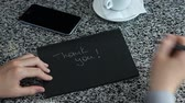 pensamientos : Female hand spelling THANK YOU with marker on black craft sketch paper laying table