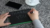 bar : Female hand spelling THANK YOU with marker on black craft sketch paper laying table