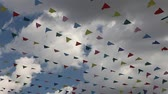 nastri colorati : Carnival celebrate banner party flags against cloudy blue sky on windy day