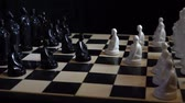 kraliçe : Slavic black and white chess pieces standing on a chessboard on a dark background. Close-up, high detail. Rotation. 4K, 25 fps. Stok Video