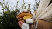 caneca : Girl with a cup of tea outdoors in winter Stock Footage
