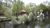 queue : Statue of Two Chinese Dragons Playing with a Pearl Fireball on a Lake at Urumqi Shuimogou Scenic Area Park