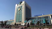 kazak : Sultans Astana City Main Railway Station Side View with Waving Kazakh Flags on a Sunny Blue Sky Day Stok Video