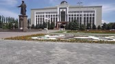 Taraz Regional Akimat City Hall with Waving Kazakh Flag on Background with Jambayev Statue of Jabayev Side View on a Sunny Blue Sky Day Stock Footage