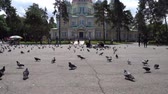 Almaty Russian Orthodox Christian Zenkov Ascension Cathedral Low Angle Frontal View in Panfilov Park with Pigeons and People on a Sunny Blue Sky Day