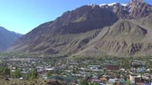 Khorugh Cityscape and Landscape with Snow Capped Mountains on the Afghanistan Side on a Sunny Blue Sky Day Stok Video