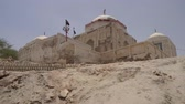 巡礼者 : Sukkur Adam Shah Ji Takri Tomb on a Low Angle Back View with Islamic Waving Flags on a Sunny Blue Sky Day
