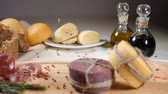 cedro : Restaurant concept. Table setting. Two pieces of cheeese decorated with rope are on wooden background with home made bread, nuts and olive bottles. Nuts and pepper fall down. Slow motion.