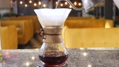 fabricado cerveja : Modern and alternative ways of coffee making.Barista brews coffee using Coffee maker Chemeks. Close up of hands pouring hot water out of pot into paper filter with Coffee. Slow motion