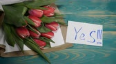 eu te amo : Top view of a Yes message note and Tulips flowers bouquet on a wooden table. Couple relationship concept. St Valentine s Day. Shot in 4 k Stock Footage
