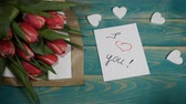 eu te amo : Top view of a I love You message note and Tulips flowers bouquet on a wooden table. Love relationship concept. St Valentine s Day. Shot in 4 k