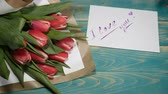 den : Top view of a I love you message note and Tulips flowers bouquet on a wooden table. Couple relationship concept. St Valentine s Day. Shot in 4 k