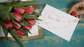 den : Top view of a I Need You message note and Tulips flowers bouquet on a wooden table. Love relationship concept. Saint Valentines Day. Shot in 4 k