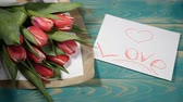 den : Top view of a Love message note and Tulips flowers bouquet on a wooden table. Love relationship concept. Saint Valentines Day. Shot in 4 k Dostupné videozáznamy