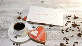 perník : Love relations. St. Valentine concept. Top view of cup of coffee and a ginger biscuit heart shaped are on wooden background with coffee beans around. Female hand puts love message note, 4 k Dostupné videozáznamy