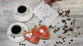 ziarna kawy : Love relations. St. Valentine concept. Top view of Two cups of coffee and two ginger biscuit heart shaped are on wooden background with coffee beans around. Female hand puts I love You message note, 4 k