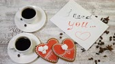 den : Top view of a I need You message note and two cups of coffee with heartshaped ginger biscuit on a wooden table. Love relationship concept. St Valentine s Day. Shot in 4 k