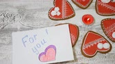 pearl : Couple relations concept. St. Valentine Day background. Heart shaped ginger biscuits,burning tea candle and pearl beads on wooden background. hand puts For You message note,Shot in 4k
