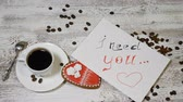 perník : Love relations. St. Valentine concept. Top view of cup of coffee and a ginger biscuit heart shaped are on wooden background with coffee beans around. hand puts I Need You message note, 4 k Dostupné videozáznamy