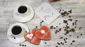 den : Saint Valentine`s Day concept. Coffee in white cups, home made heart shaped ginger biscuit on wooden background. hand puts I Love You message note, 4 k